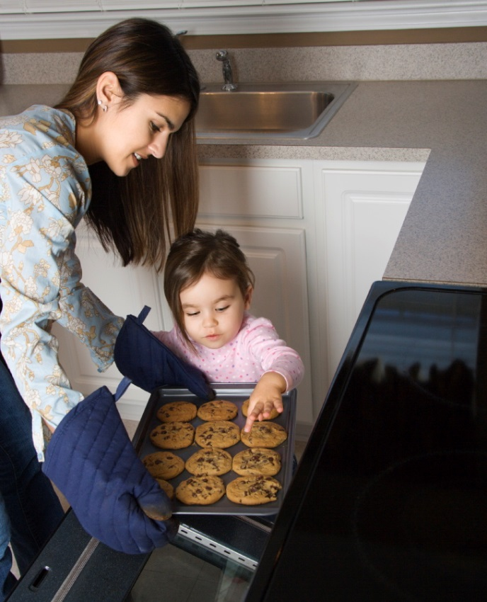 Woman baking cookies with young girl